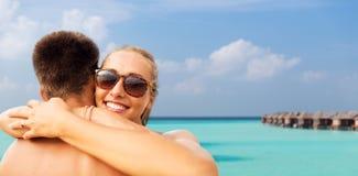 拥抱在夏天海滩的愉快的夫妇 免版税图库摄影