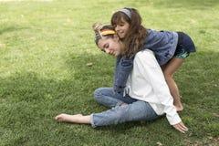 拥抱在她的姐妹后的女孩 免版税库存图片