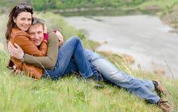 拥抱在小山的爱恋的年轻夫妇冠上 库存照片