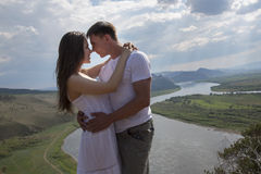 拥抱在山的年轻夫妇 免版税库存照片