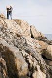 拥抱在岩石的成熟夫妇 免版税图库摄影