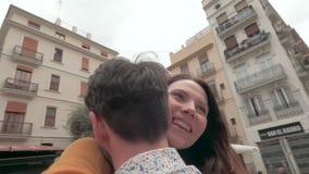 拥抱在巴伦西亚广场的一对愉快的夫妇的一个慢动作 影视素材