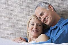 拥抱在床上的夫妇 免版税库存照片