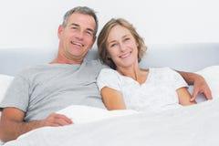 拥抱在床上的愉快的夫妇看照相机 免版税库存照片