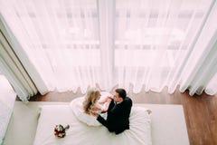 拥抱在床上的新婚佳偶在豪华轻的旅馆客房 免版税库存照片