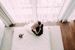 拥抱在床上的新婚佳偶在豪华轻的旅馆客房 免版税库存图片