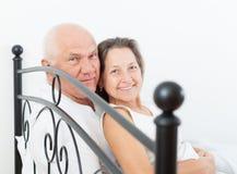拥抱在床上的年长夫妇 图库摄影