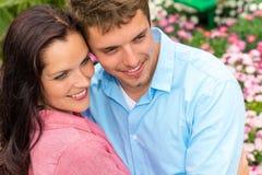 拥抱在开花的庭院里的愉快的夫妇 图库摄影