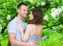 拥抱在开花的树附近的俏丽的夫妇 库存图片