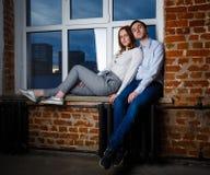 拥抱在日落天空的背景的窗台的愉快的年轻夫妇在窗口里 免版税库存照片