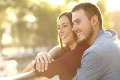 拥抱在日落的夫妇在阳台上 免版税库存照片