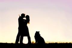 拥抱在日落的爱恋的年轻夫妇剪影外面 免版税库存照片