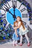拥抱在时钟旁边的姐妹 圣诞前夕礼品节假日许多装饰品 免版税库存图片