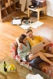 拥抱在有膝上型计算机的长沙发的年轻夫妇 免版税库存图片