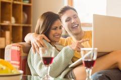 拥抱在有膝上型计算机的长沙发的年轻夫妇 免版税图库摄影