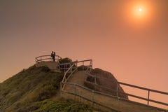 拥抱在有雾的日落Muir海滩的浪漫夫妇俯视 免版税库存照片