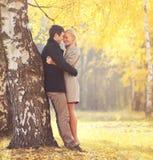 拥抱在树附近的愉快的年轻爱恋的夫妇在秋天 免版税库存图片