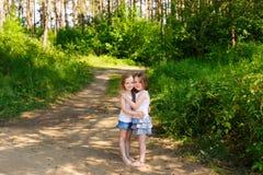 拥抱在森林里的两个小女孩女朋友 免版税库存照片