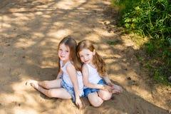 拥抱在森林里的两个小女孩女朋友 免版税库存图片