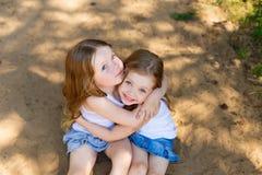 拥抱在森林里的两个小女孩女朋友 免版税图库摄影