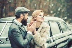 拥抱在森林里的时髦的爱恋的婚礼夫妇在减速火箭的汽车附近 免版税库存图片