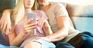 拥抱在沙发的无法认出的夫妇检查智能手机在他们的现代家 拿着手机的妇女,浏览网 免版税库存图片