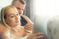 拥抱在沙发的时髦的夫妇使用数字式片剂在他们的现代家 拿着片剂的妇女,浏览网 免版税库存照片