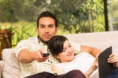 拥抱在沙发的逗人喜爱的夫妇,当看电视时 免版税图库摄影
