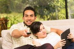 拥抱在沙发的逗人喜爱的夫妇,当看电视时 免版税库存图片
