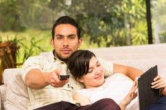 拥抱在沙发的逗人喜爱的夫妇,当看电视时 免版税库存照片