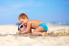 拥抱在沙子的愉快的孩子父亲的头在海滩 免版税图库摄影