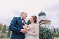 拥抱在浪漫绿色公园的热情的新婚佳偶在古色古香的修道院附近 低角度视图 库存图片