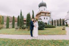 拥抱在浪漫绿色公园的热情的新婚佳偶在古色古香的修道院附近 免版税库存照片