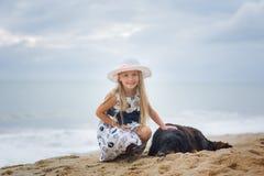拥抱在海滩的帽子的逗人喜爱的女孩一条狗 免版税库存图片