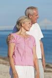 拥抱在海滩的愉快的浪漫高级夫妇 库存照片