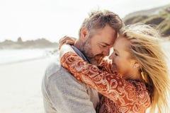 拥抱在海滩的爱恋的资深夫妇 免版税库存图片