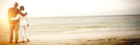 拥抱在海滩的资深夫妇背面图  免版税库存照片