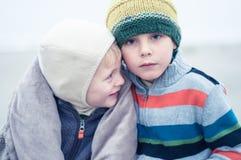 拥抱在海滩的两个兄弟 免版税图库摄影