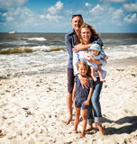 拥抱在海滩的家庭 库存图片