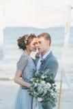 拥抱在海滨的新婚佳偶 库存照片