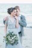 拥抱在海滨的新婚佳偶 免版税库存照片