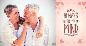 拥抱在海滩的有吸引力的已婚夫妇的综合图象 免版税库存图片