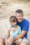 拥抱在海滩的父亲和儿子 免版税图库摄影
