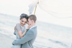 拥抱在海滨的高兴新婚佳偶 库存照片