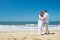 拥抱在海滩的年轻浪漫夫妇 免版税库存图片
