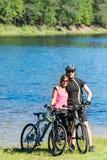拥抱在湖边的少年骑自行车的人 免版税库存图片