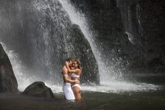 拥抱在瀑布之下的夫妇 免版税库存照片