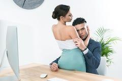 拥抱在爱抚的买卖人热情的夫妇在工作场所在办公室 库存图片