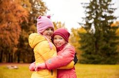 拥抱在秋天公园的两个愉快的小女孩 库存图片