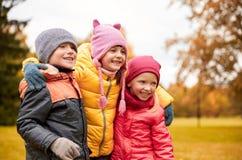 拥抱在秋天公园的小组愉快的孩子 免版税库存图片